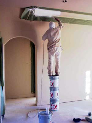 man standing on three paint cans to paint a ceiling fixture